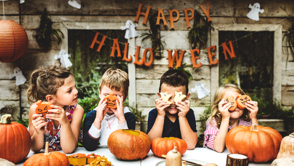 kids sitting by pumpkins holding up Halloween cookies
