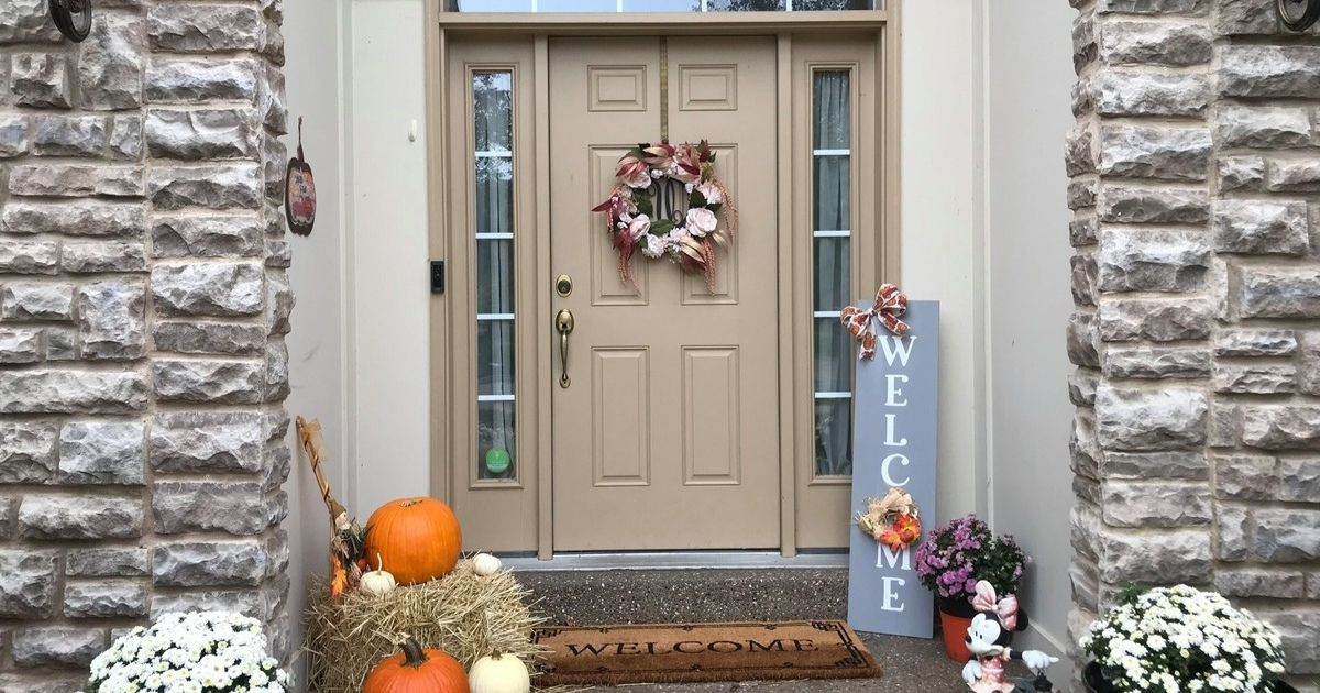 front porch with festive WELCOME sign and pumpkins and fall decor