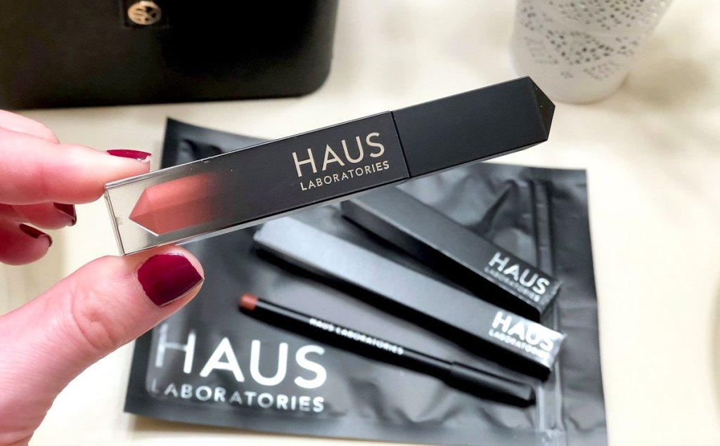 woman holding up haus laboratories liquid lipstick with other lip products in background