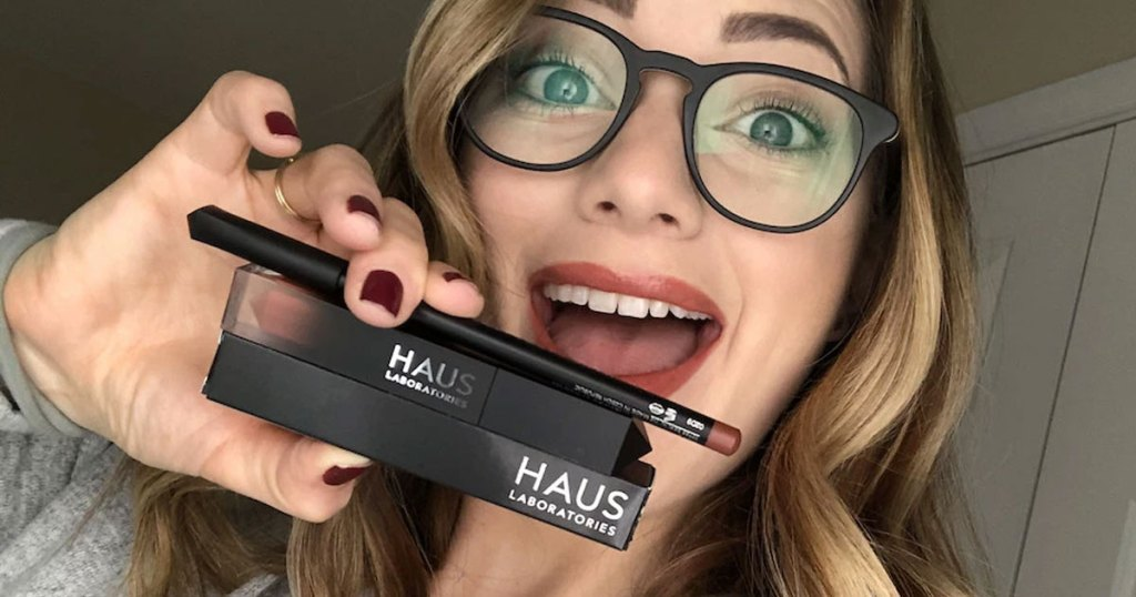 woman with blonde hair and black glasses holding up haus laboratories liquid lip gloss and lip pencil