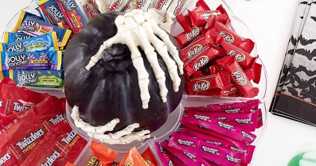 bowl of hersheys halloween candy with skeleton hands