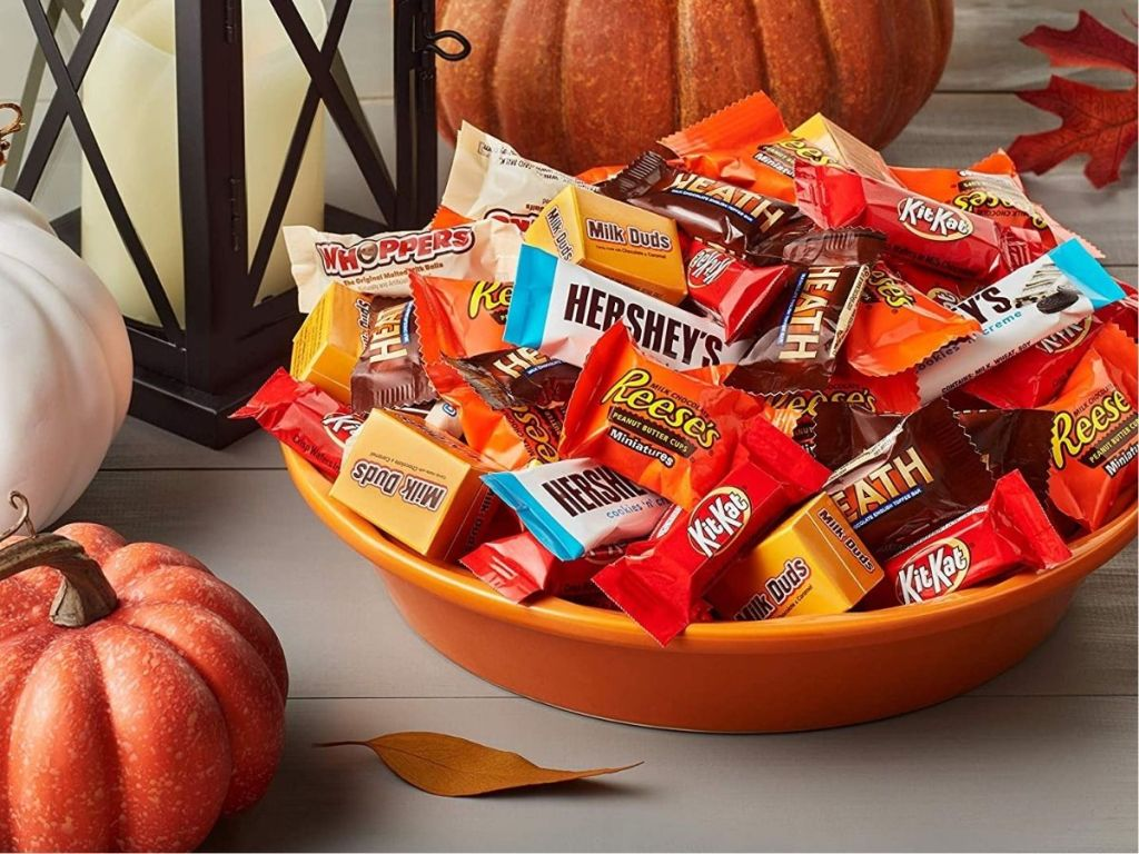 chocolate candy in orange bowl with pumpkins near bowl
