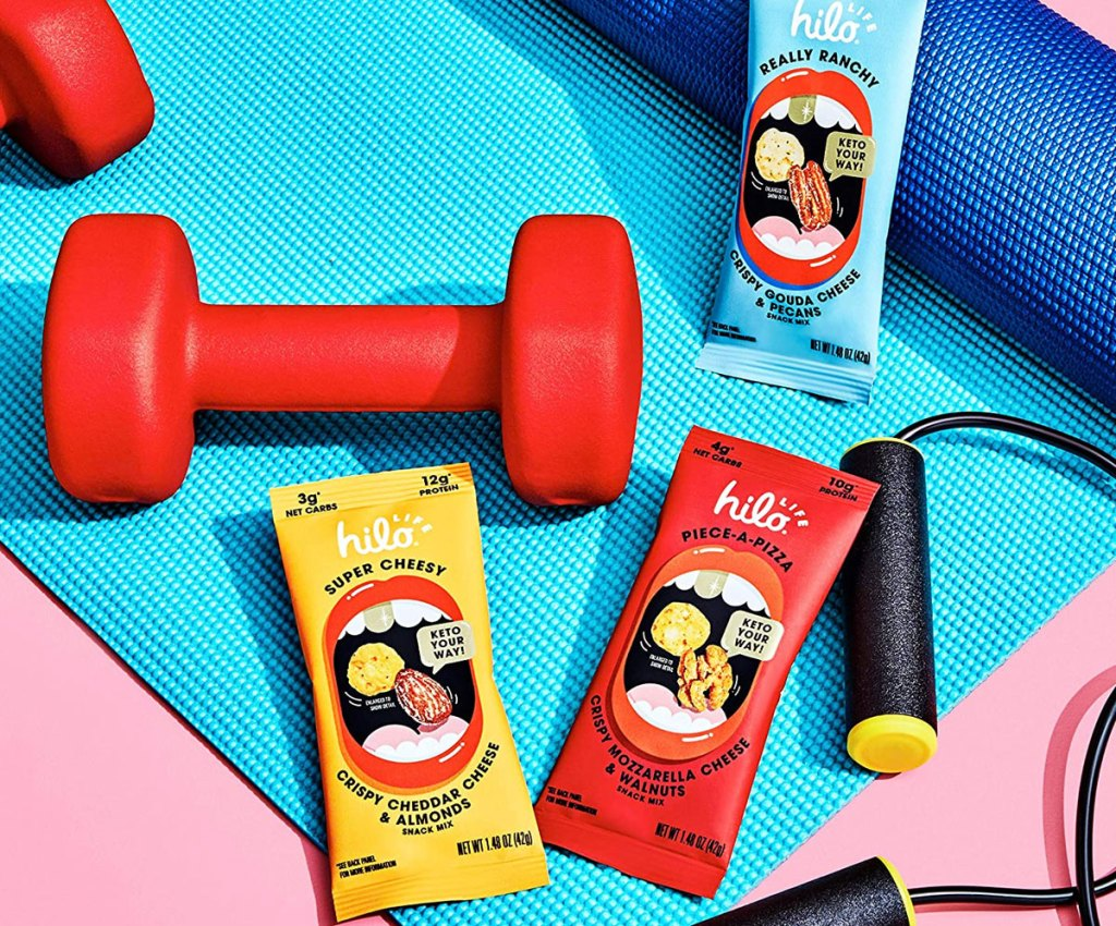 yellow, red, and blue pouches of snack mixes on yoga mat near hand weights and jump rope