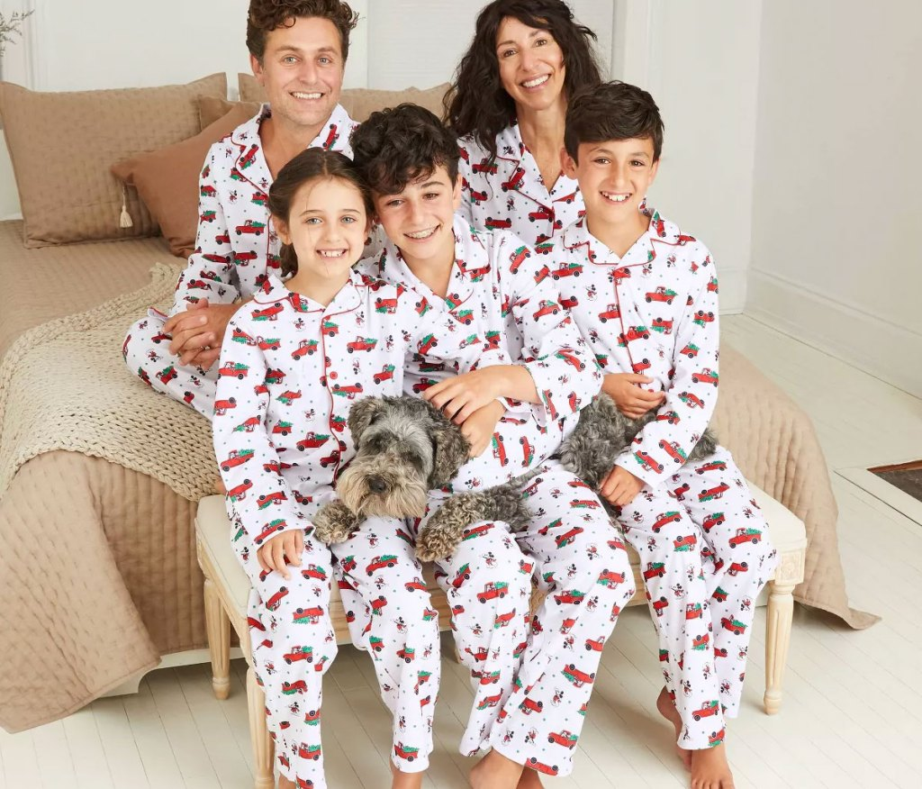 family wearing matching white and red mickey mouse christmas pajamas