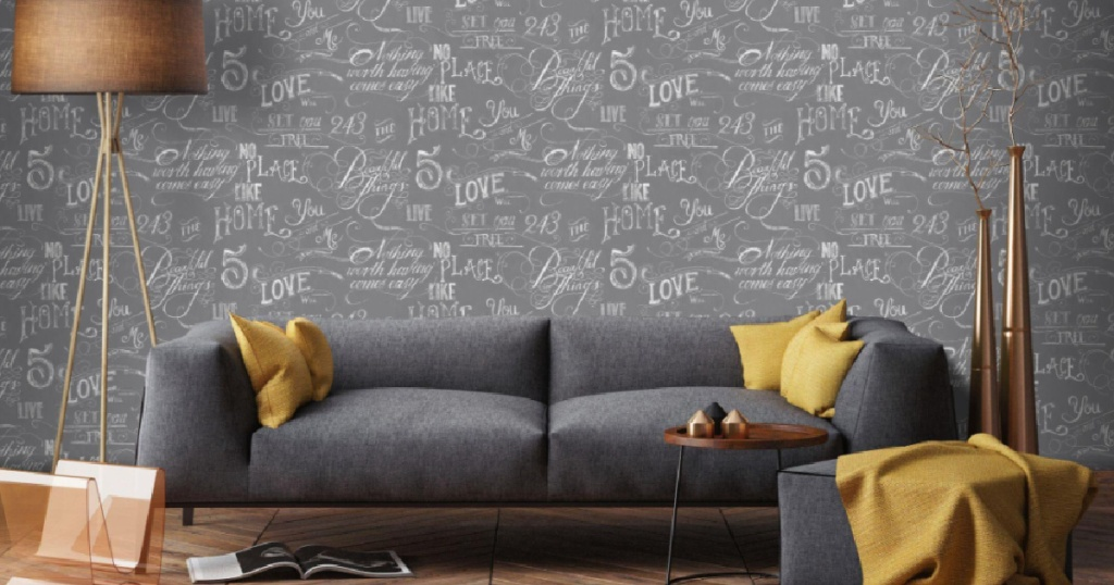 dark grey couch with grey and white wallpaper lamp and throw blankets