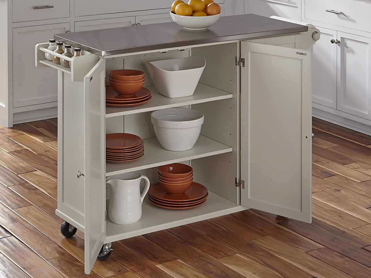 off-white kitchen cart filled with dishes in kitchen and bowl of oranges