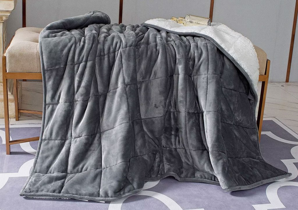 grey micro-mink weighted blanket with white sherpa interior draped on an ottoman