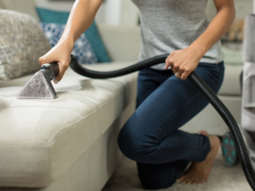 woman using vacuum attachment on couch
