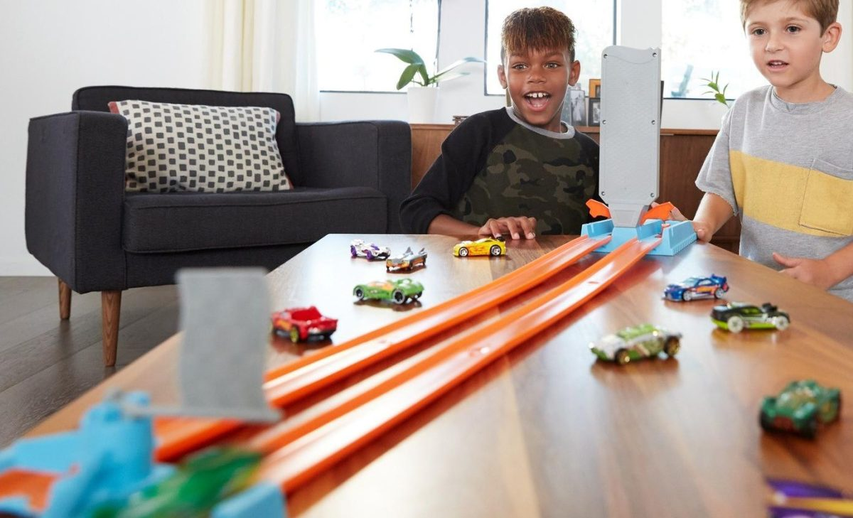 two boys playing with vehicle playset on table in living room