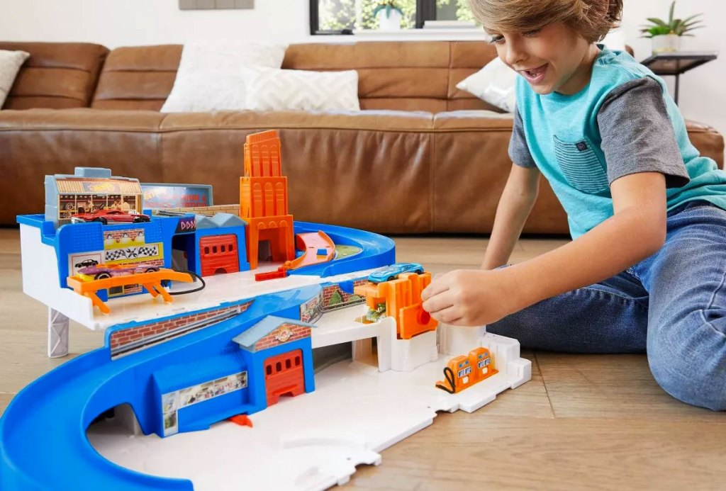 boy playing with blue and orange hot wheels track set on floor