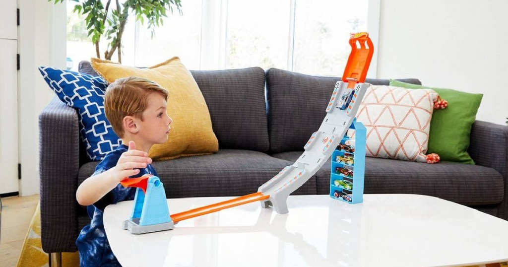 boy playing with vehicle playset on table in living room