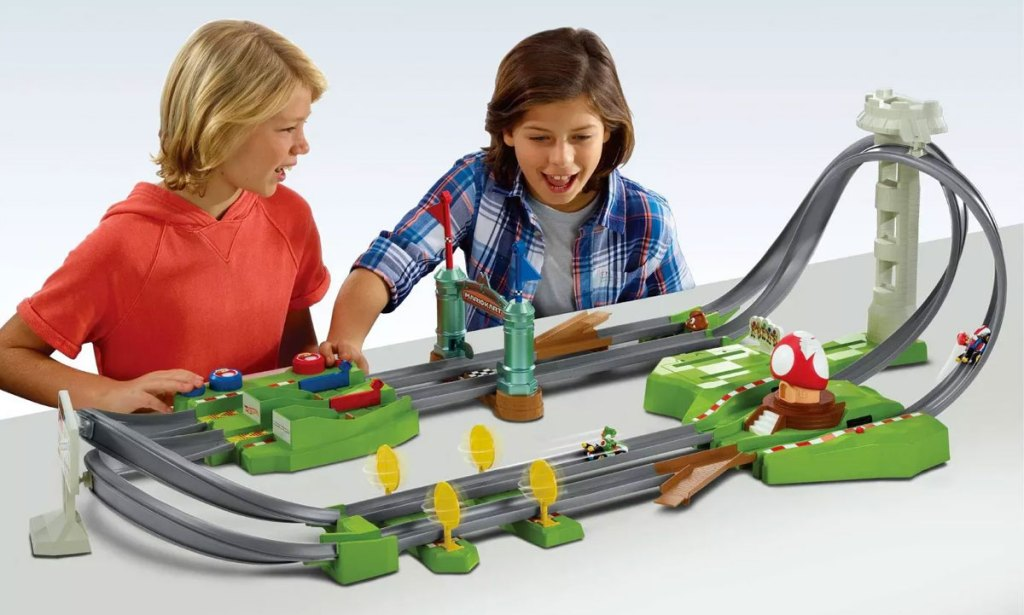 two kids playing with hot wheels mario kart track set