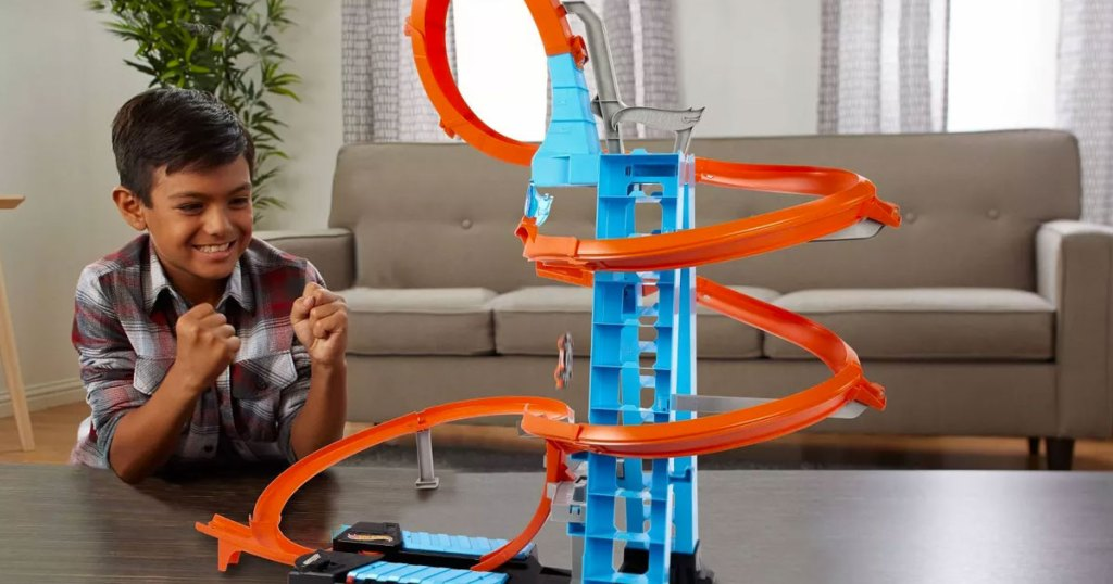 boy playing with a tall blue and orange hot wheels track set