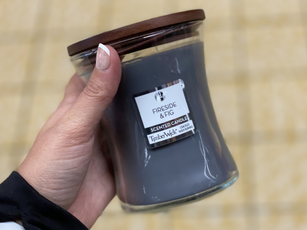 manicured hand holding fireside and fig scented candle