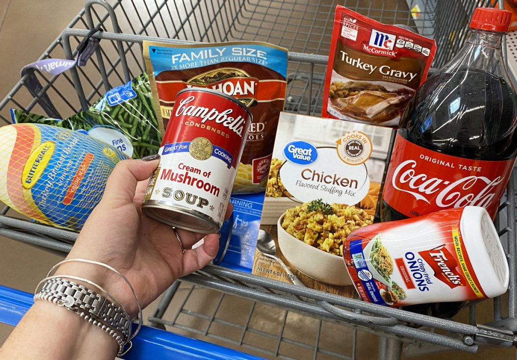 walmart shopping cart full of thanksgiving dinner items with woman holding up can of campbell's cream of mushroom soup