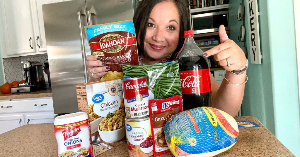 woman holding instant potatoes and pointing at thanksgiving dinner ingredients on kitchen counter in front of her