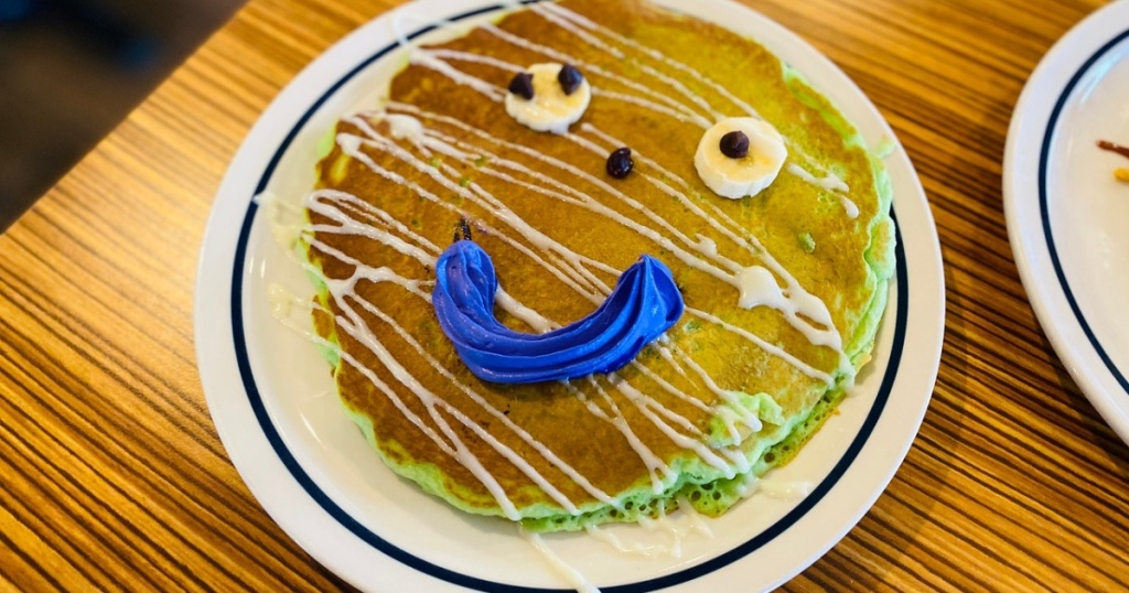 table with pancake with frosting and smile on it