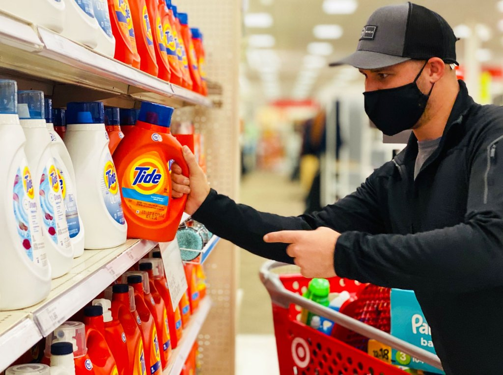 man wearing black jacket and face mask grabbing an orange bottle of tide off target shelf