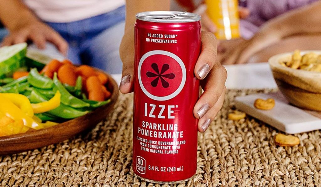 hand holding a can of Izze juice on a table