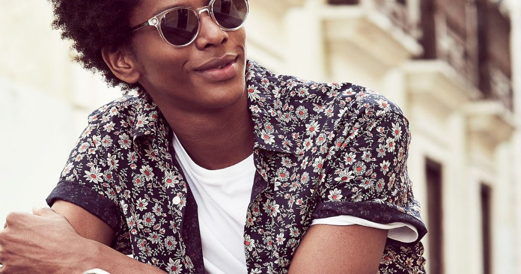man wearing sunglasses and floral print button up shirt with white undershirt