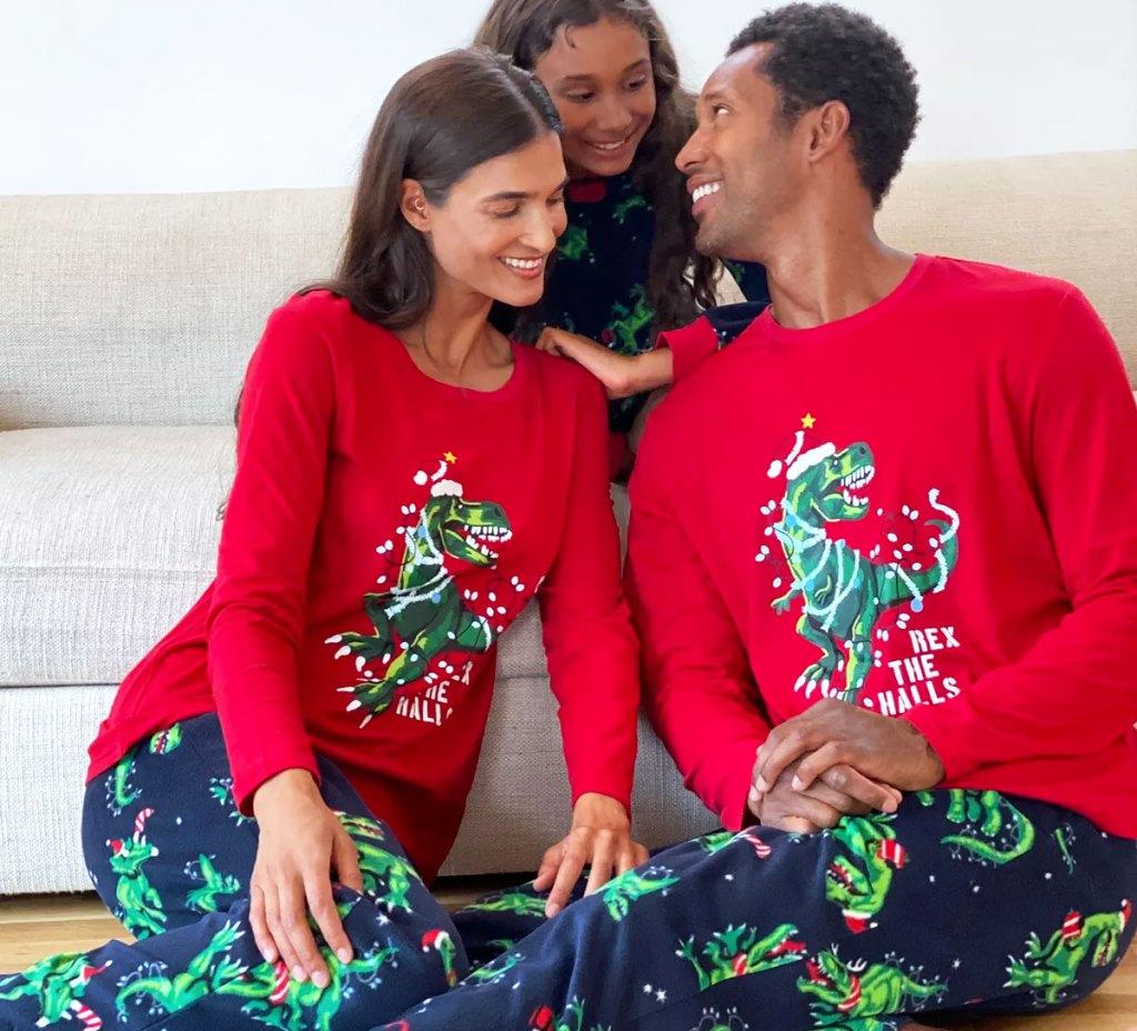 family wearing matching christmas dino print pajamas