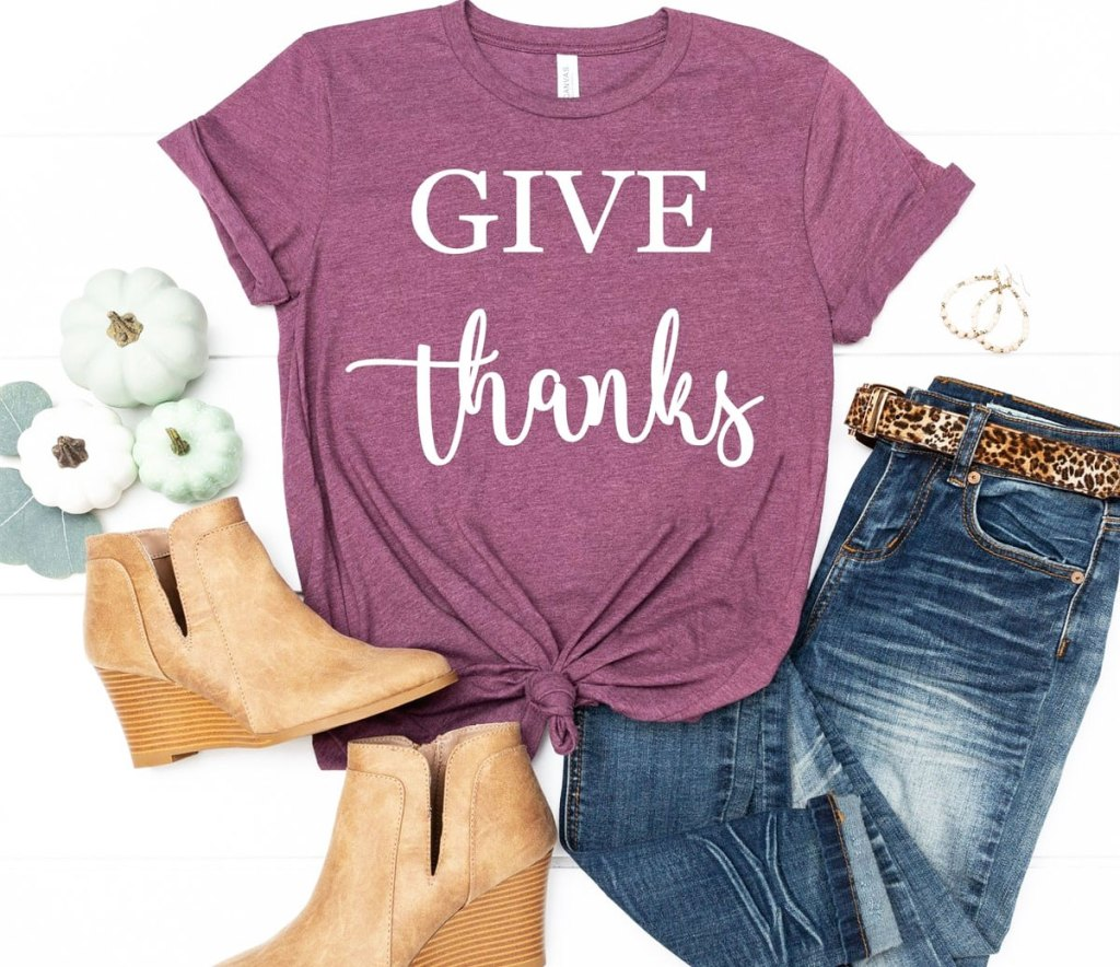 purple tee that says give thanks styled with pair of jeans and ankle boots