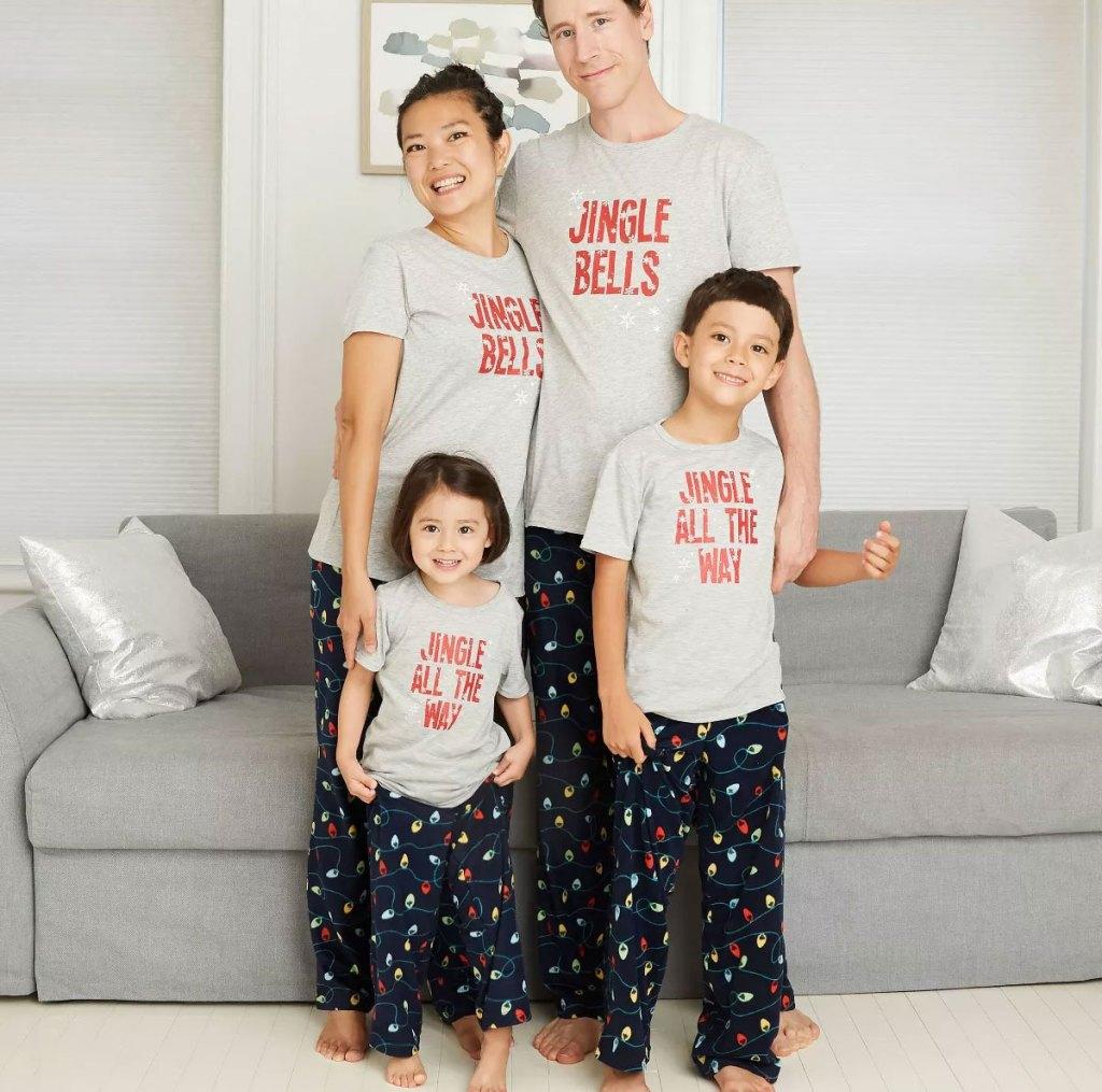 family wearing matching jingle bells t-shirts and holiday lights printed pajamas pants
