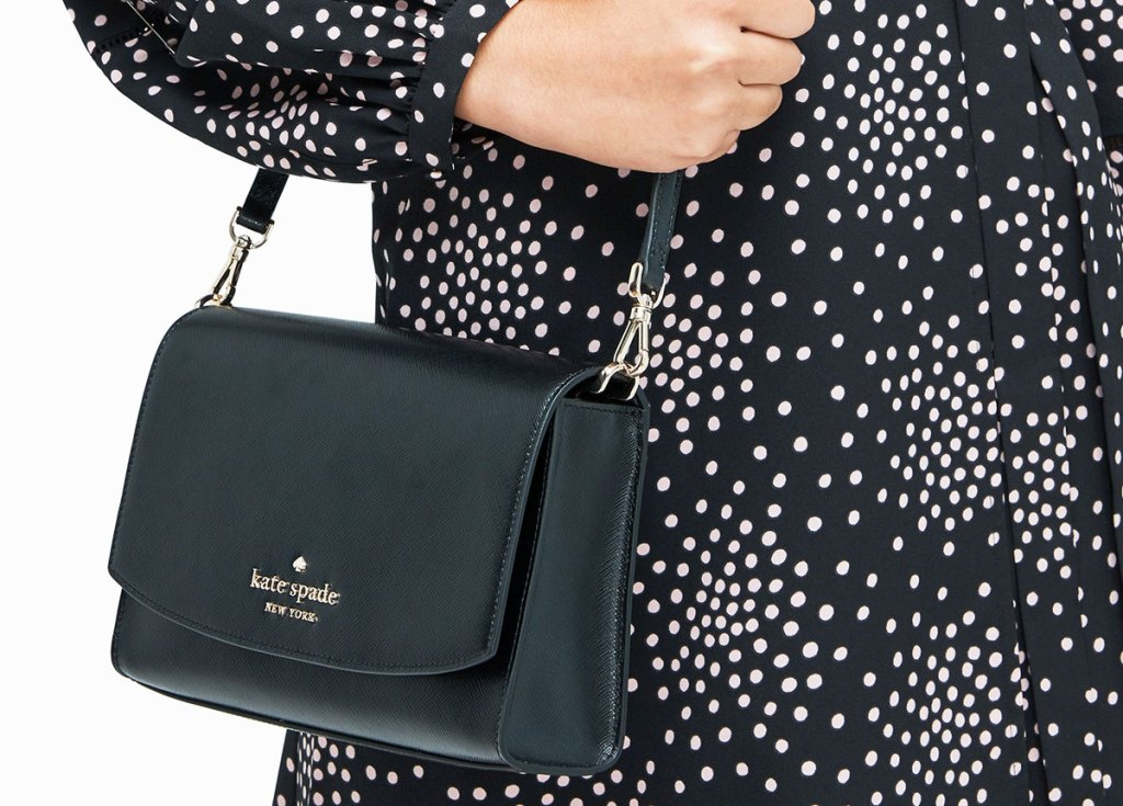 woman wearing a black and white printed long sleeve dress with a black kate spade crossbody bag