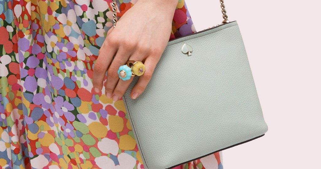 woman wearing floral print dress and mint green crossbody bag