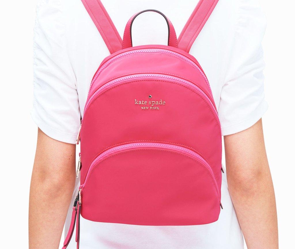 woman wearing a shite t-shirt and print pink kate spade nylon backpack