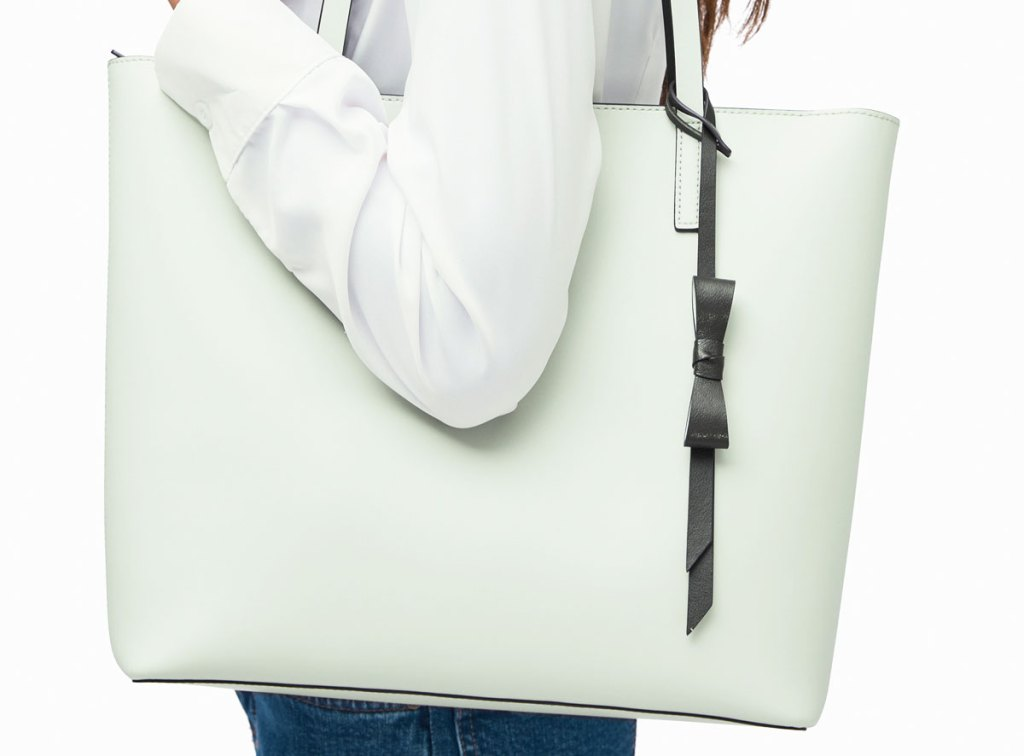 woman wearing a mint green kate spade tote bag on shoulder with a black bow detail
