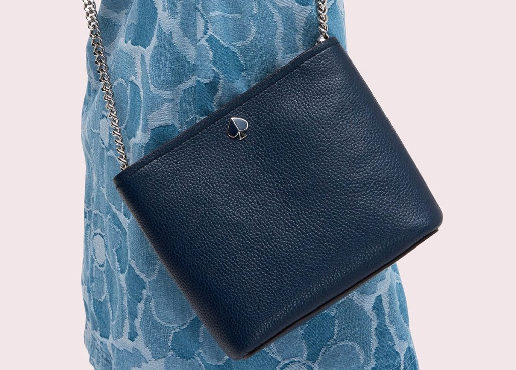 woman in blue dress with navy blue kate spade crossbody bag