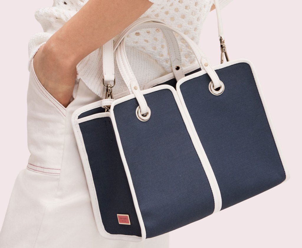 woman wearing a navy blue with white details satchel on her shoulder