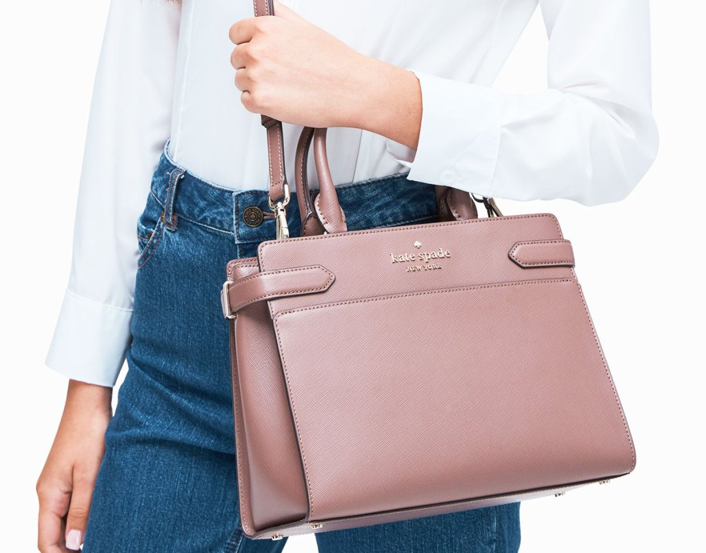 woman wearing white top tucked into jean with mauve colored satchel purse