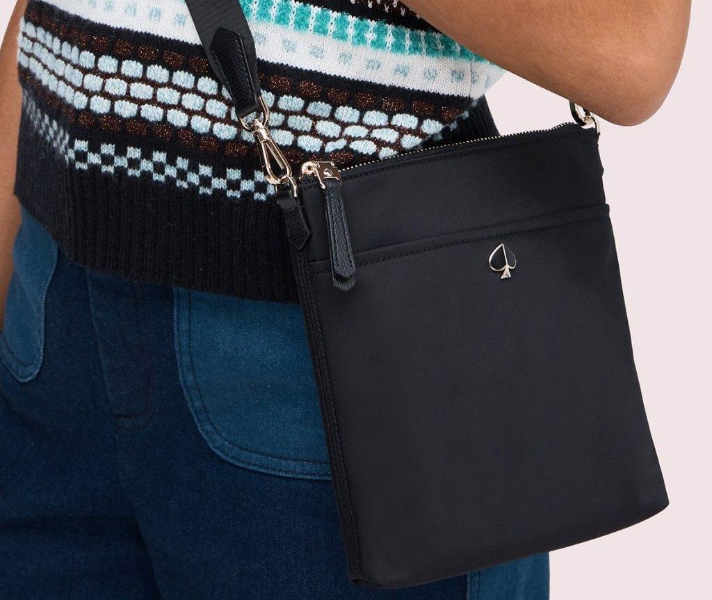 woman wearing a black kate spade crossbody bag