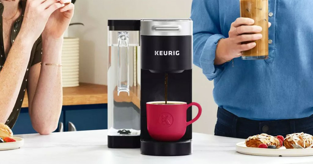 black keurig coffee maker brewing into red cup with people behind it in kitchen