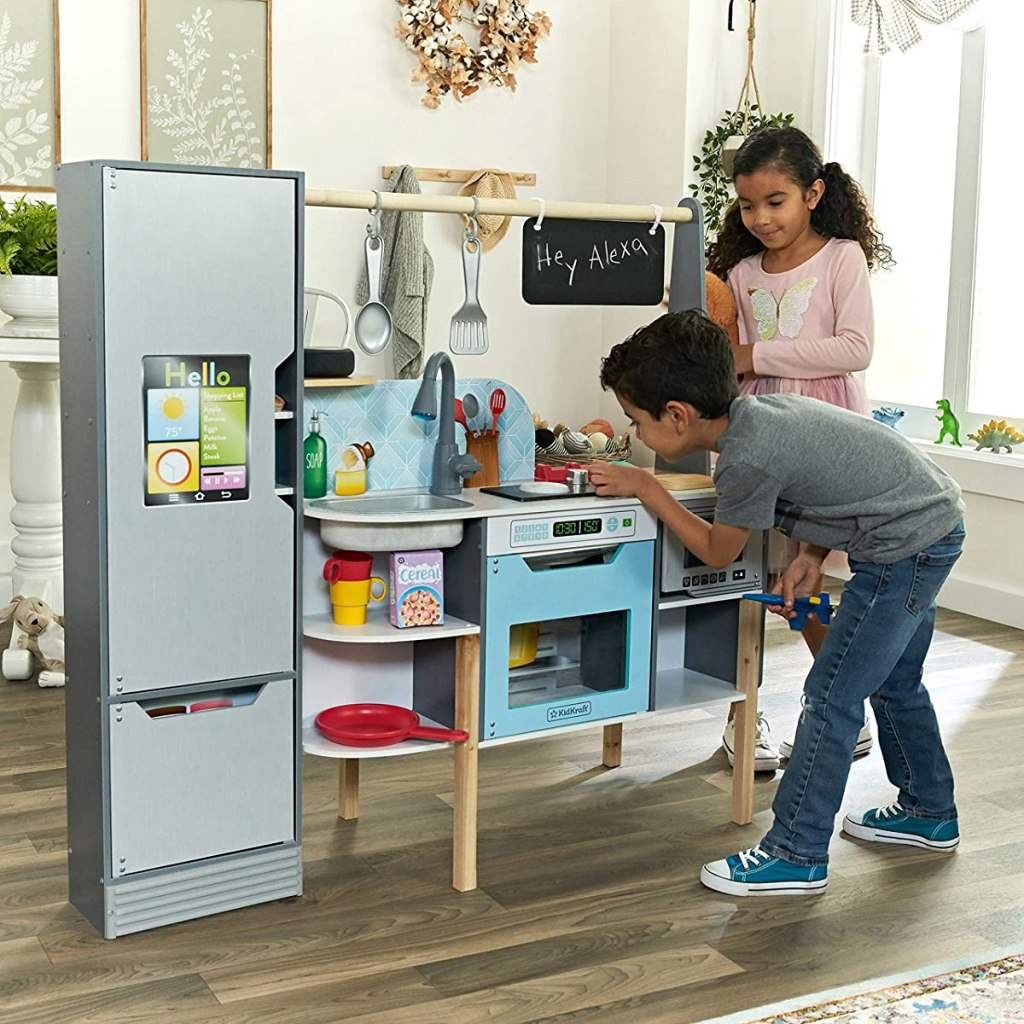 kids playing in a toy kitchen