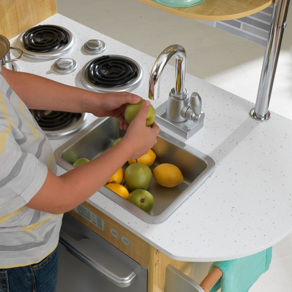 boy washing produce in a pretend sink