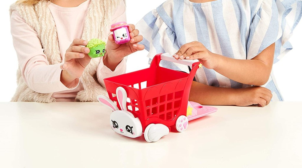 girls playing with a toy shopping cart