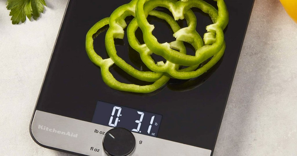 black and stainless steel cooking scale with green bell pepper slices on it
