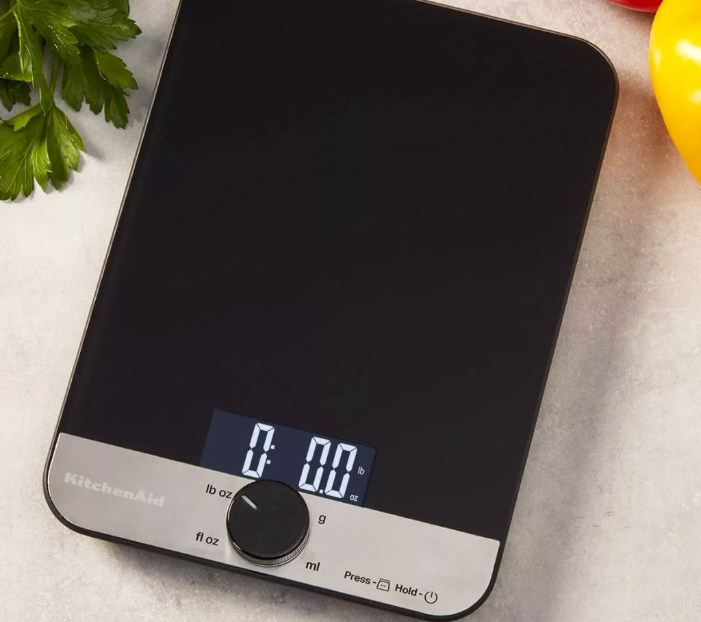 black and stainless steel kitchen scale on counter near cilantro and yellow pepper