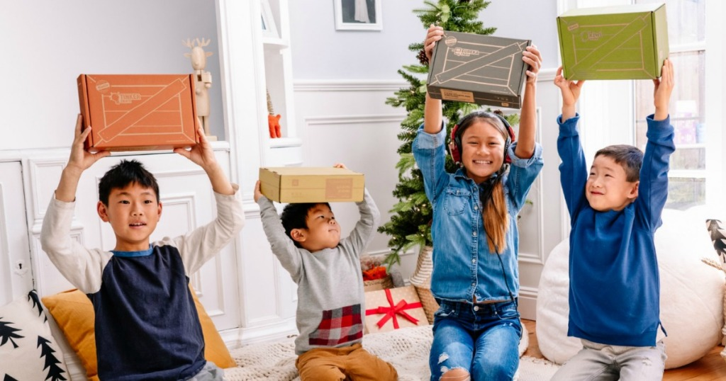 empat anak memegang kotak di sebuah ruangan dengan dekorasi natal