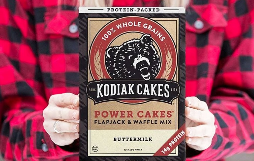 woman in red and black plaid shirt holding up box of kodiak cakes protein pancake mix