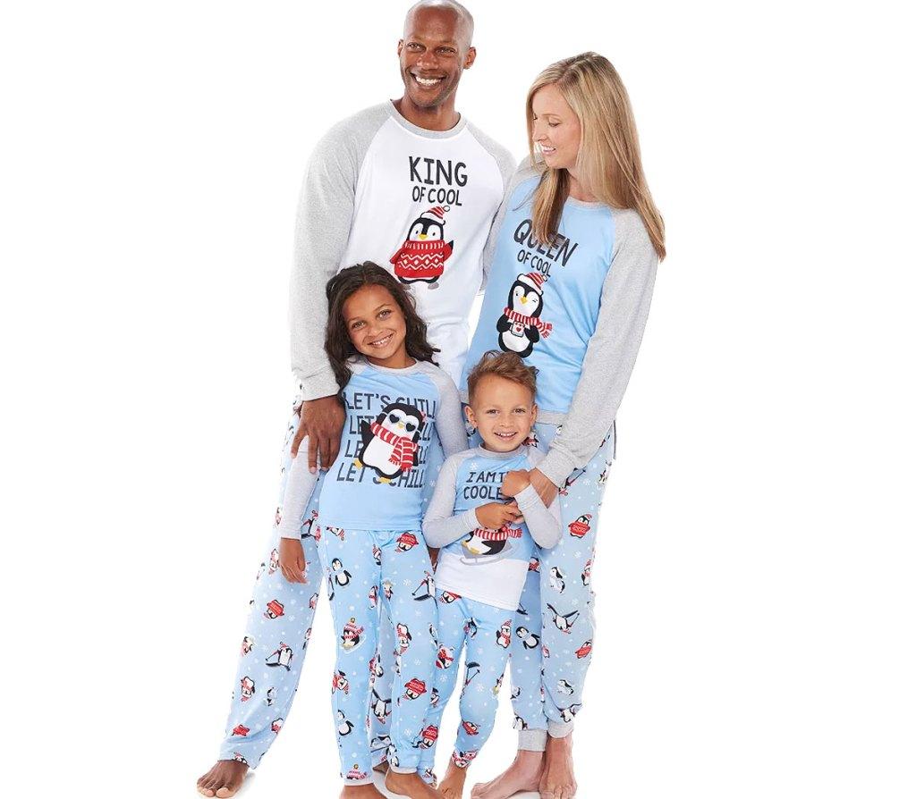 family of four weaing matching light blue penguin pajama sets