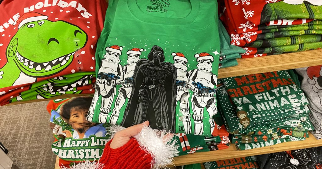 person in red and white santa gloves holding folded green star wars storm trooper and darth vader graphic tee