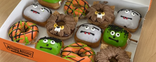 dozen Halloween-themed doughnuts in orange box on table