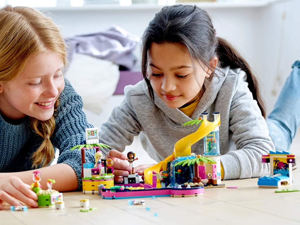two girls playing with building toy set on floor