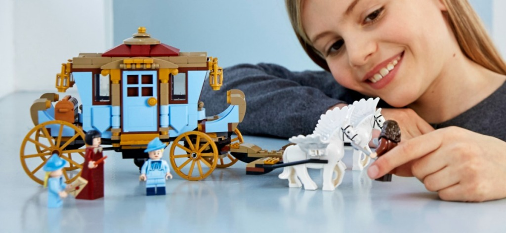girl playing with LEGO carriage