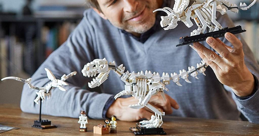 man holding dinosaur fossil building kit
