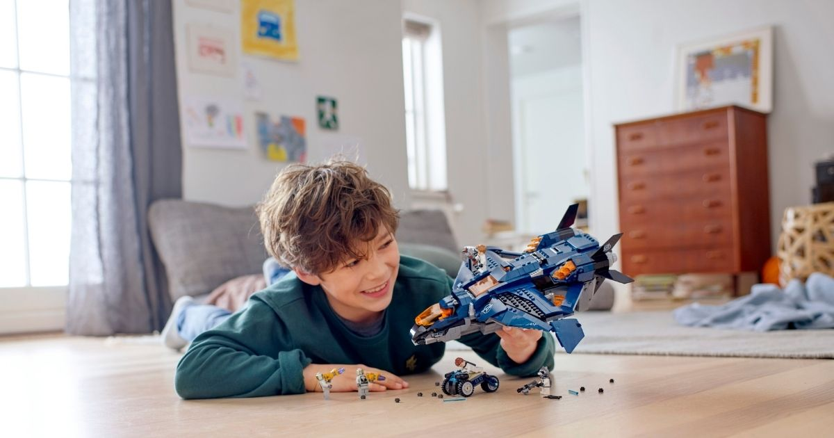 boy playing with LEGO jet and accessories on floor of room